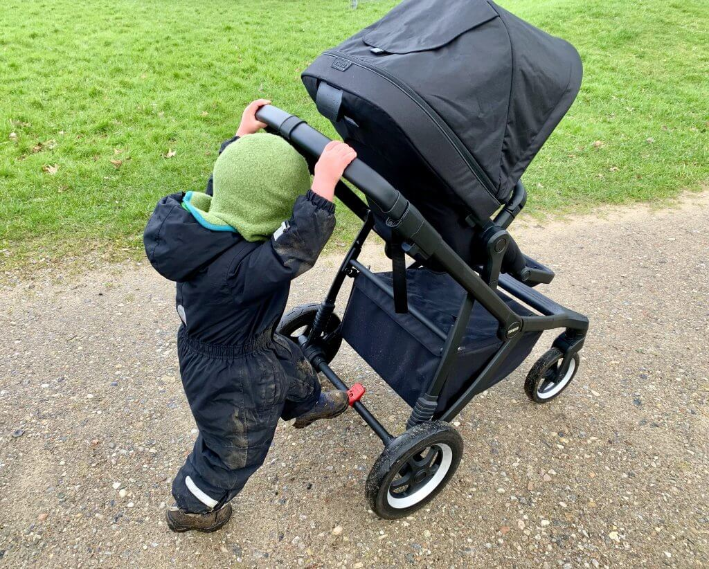 Kind schiebt Kinderwagen