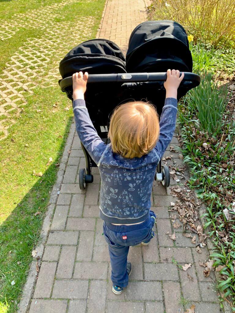 Kind schiebt Kinderwagen